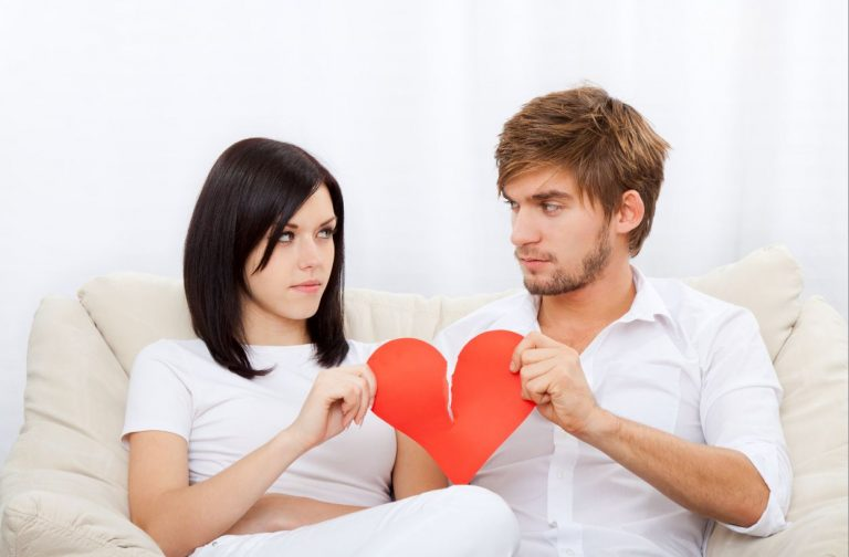 An unhappy couple holding two sides of a ripping heart. Blog author speaks about how a bad relationship can lead to enlightening.